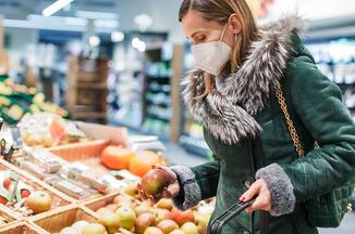 Masked shopper browsing the fresh fruit aisle of a supermarket