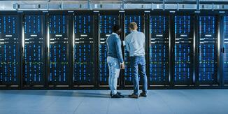 Two people examining a server rack