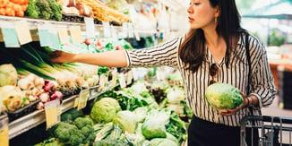 Woman choosing fresh vegetables at grocery retailer