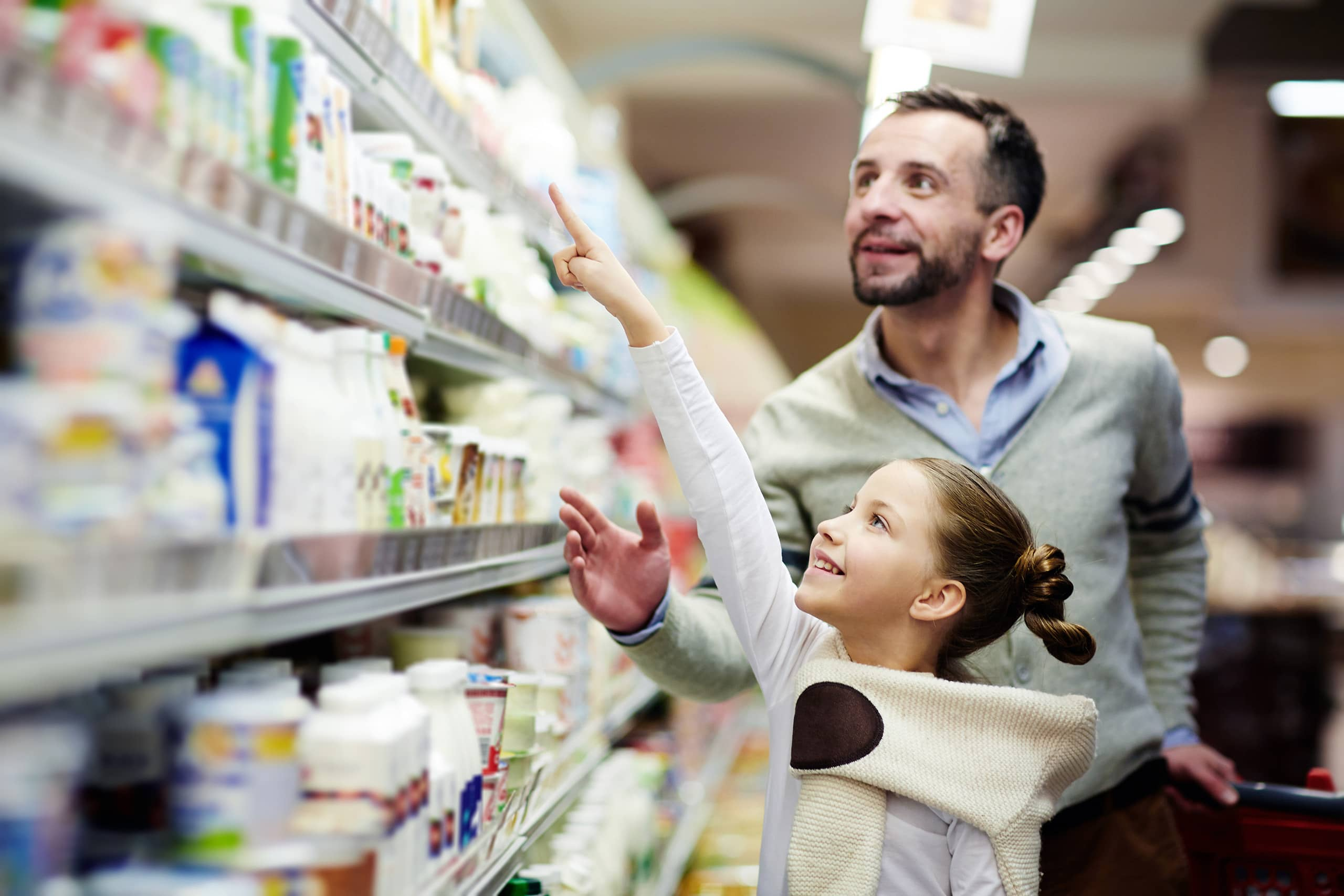 Man and young girl food shopping at grocery retail